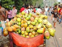 被卖在繁忙的市场领域的巨大的堆椰子 库存图片