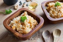 被发酵的圆白菜和红萝卜在两个木碗 免版税库存照片