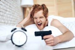 被叫醒的邪恶的人是目标开枪在闹钟 免版税图库摄影