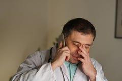 被吸收的医生画象谈话在他的手机 免版税库存照片