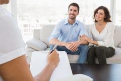 被和解的夫妇微笑和谈话与他们的治疗师 免版税库存图片