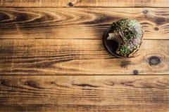 被咬住的多福饼用在木背景的巧克力 免版税库存照片