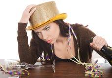 年轻被喝的妇女由桌和有空的瓶的。 免版税图库摄影
