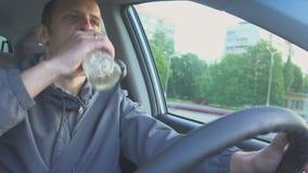 被喝的驱动器 人射击的关闭喝伏特加酒,当在汽车时 在路的危险 股票录像