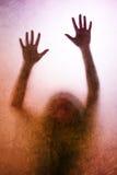 被困住的妇女,后面点燃了手剪影在表面无光泽的玻璃后的 库存图片