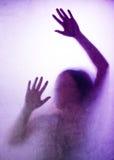 被困住的妇女,后面点燃了手剪影在表面无光泽的玻璃后的 免版税库存照片