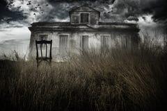 被困扰的房子和椅子 免版税库存照片