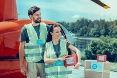 被围拢与箱子的快乐的悦目勤勉志愿者 库存照片