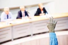 被培养的人的手在业务会议期间 投票为了和反对 免版税库存照片