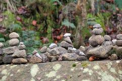 被堆积的小卵石和岩石在一个大青苔在秋天森林地盖了冰砾 图库摄影