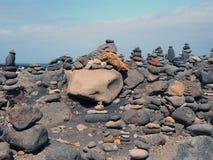 被堆积的小卵石和石头塔用不同的颜色在一个大安排在黑沙子靠岸与蓝天 库存照片