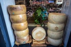 被堆积的巴马干酪Reggiano形式,在销售中的最著名的意大利乳酪在商店 图库摄影