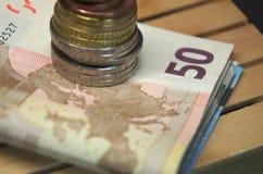 被堆积的欧洲钞票和硬币金钱在板台 储蓄 库存照片