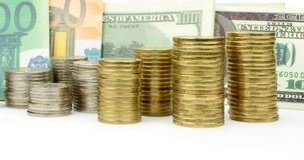 被堆积的硬币、欧元和美元钞票 库存图片