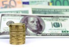 被堆积的硬币和钞票背景 库存照片