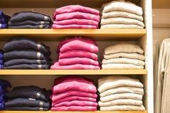 被堆积的精神毛线衣在零售地方 免版税库存照片