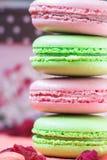 被堆积的,鲜美桃红色和绿色蛋白杏仁饼干,五颜六色的可口法式酥皮点心、草莓和开心果蛋白杏仁饼干 图库摄影