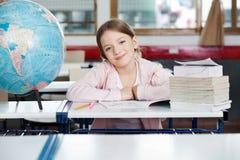 被堆积逗人喜爱的女小学生坐与地球和 免版税库存图片