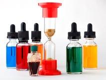 被填装的玻璃瓶上色了与吸管和滴漏的液体在白色背景 库存照片