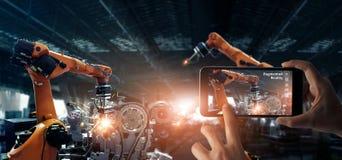 被增添的现实产业概念 举行流动智能手机用途AR应用的手检查和控制焊接的机器人学 免版税库存图片
