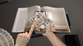 被增添的现实概念 递拿着有AR应用的智能手机用于模仿3d突然出现交互式房子地图 免版税库存照片