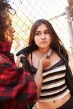 被威胁与刀子的女孩由女性帮会成员 免版税库存图片