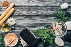 被安排的小卵石顶视图,盐、油,竹棍子和兰花在温泉和按摩的碗开花 免版税图库摄影