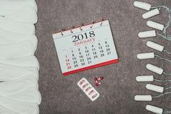 被安排的月经垫和棉塞、日历和药片灰色表面上 库存图片