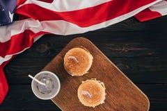 被安排的汉堡和苏打饮料顶视图与美国国旗在木桌面 库存照片