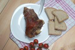 被安排的火腿飞腓节照片一头猪用面包和西红柿 在视图之上 木书桌 免版税库存照片