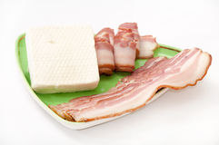 被安排的烟肉和希腊白软干酪在一块绿色板材 免版税库存图片