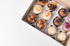被安排的鲜美杯形蛋糕顶视图在纸板箱的 免版税库存图片