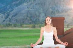 被定调子的妇女的综合图象莲花姿势的在健身演播室 免版税图库摄影