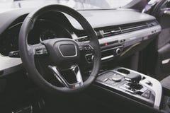 被定调子的强表面无光泽 现代豪华汽车内部多方向盘、转移杠杆和仪表板 免版税库存图片