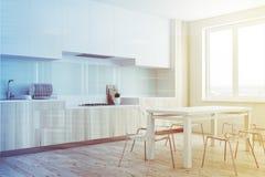 被定调子的木餐厅和厨房角落 免版税库存照片