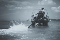 被定调子的黑白暗淡 longtail汽艇的司机驾驶有远射和推进器的一个马达 桔子的水手 免版税库存图片
