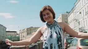 被察觉的礼服的快乐的女孩在老市中心涂了胳膊在堤防 影视素材