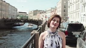 被察觉的礼服的快乐的女孩沿河在老市中心唱歌 影视素材