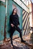 被射击的时尚:美丽的在长袍和皮革的岩石女孩不拘形式的模型画象气喘身分在金属门 免版税库存照片
