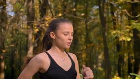 被射击的移动式摄影车,在年轻亭亭玉立的女孩档案的特写镜头画象去跑步在秋季公园的连衫裤的 股票视频