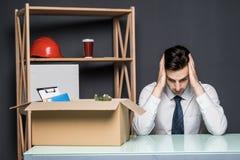 被射击的获得 在衣服的英俊的商人哀伤地坐在桌上在办公室靠近有他的材料的箱子 免版税图库摄影