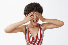 被射击镶边成套装备的感情悦目非洲妇女,感到愉快和发笑的演播室,盖眼睛用棕榈 免版税库存照片