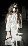 被射击的恐怖样式:有moppet玩偶和刀子的奇怪的哀伤的女孩在手上 免版税库存照片
