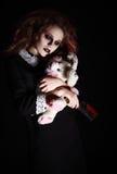 被射击的恐怖:有兔子玩具和血淋淋的刀子的哀伤的哥特式女孩在手上 免版税库存照片