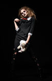 被射击的恐怖:有兔子玩具和血淋淋的砍肉刀的可怕妖怪女孩在手上 图库摄影