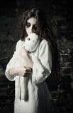 被射击的恐怖:有moppet玩偶的哀伤的奇怪的女孩在手上 免版税图库摄影