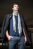 被射击的时尚:英俊的年轻人佩带的牛仔裤、外套、衬衣和围巾 库存图片