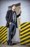 被射击的时尚:英俊的年轻人佩带的牛仔裤和外套 库存图片