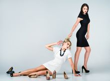 被射击的演播室时尚:两名逗人喜爱的妇女的交锋(白肤金发和深色) 库存照片