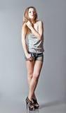 被射击的演播室时尚:美丽的女孩佩带的牛仔布短裤和衬衣 库存图片
